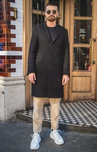 Combinar un pantalón chino de pana marrón claro: Emparejar un abrigo largo negro con un pantalón chino de pana marrón claro es una opción incomparable para un día en la oficina. ¿Quieres elegir un zapato informal? Usa un par de deportivas blancas para el día.