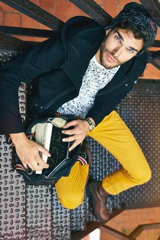 Cómo combinar: botas casual de cuero marrónes, pantalón chino mostaza, camiseta con cuello circular estampada en blanco y azul marino, abrigo largo azul marino