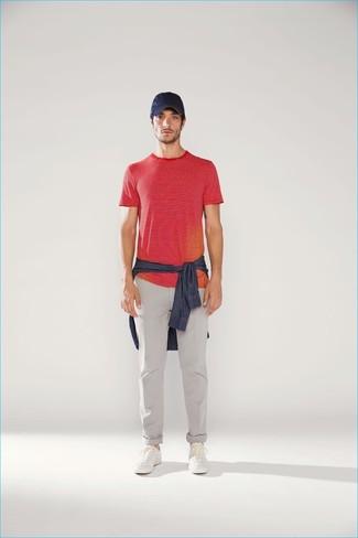 Cómo combinar: tenis de cuero blancos, pantalón chino gris, camiseta con cuello circular de rayas horizontales roja, camisa vaquera azul marino