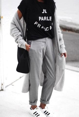 Cómo combinar: tenis de cuero en blanco y negro, pantalón chino gris, camiseta con cuello circular estampada en negro y blanco, cárdigan largo gris