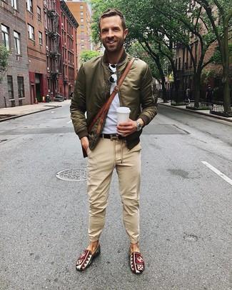 Cómo combinar: zapatillas slip-on de lona estampadas en multicolor, pantalón chino marrón claro, camiseta con cuello circular gris, cazadora de aviador verde oliva