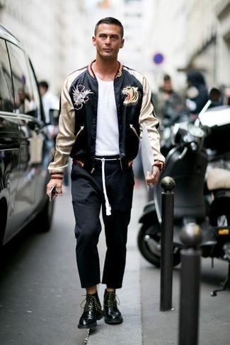 Outfits hombres: Para un atuendo que esté lleno de caracter y personalidad elige una cazadora de aviador estampada negra y un pantalón chino negro. Opta por un par de botas casual de cuero negras para mostrar tu inteligencia sartorial.