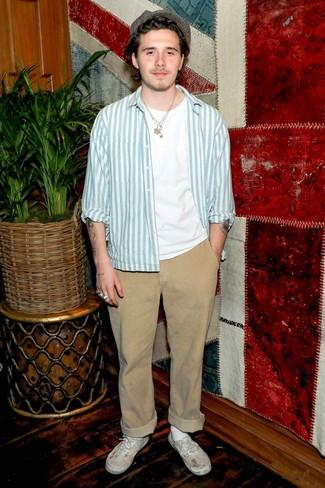 Look de Brooklyn Beckham: Tenis de lona blancos, Pantalón chino marrón claro, Camiseta con cuello circular blanca, Chaqueta estilo camisa de rayas verticales celeste