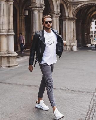 Cómo combinar: tenis de cuero en blanco y negro, pantalón chino de rayas verticales gris, camiseta con cuello circular en blanco y negro, chaqueta motera de cuero negra