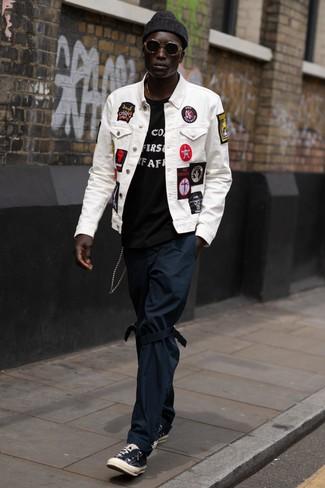 Cómo combinar: tenis de lona negros, pantalón chino azul marino, camiseta con cuello circular estampada en negro y blanco, chaqueta vaquera bordada blanca