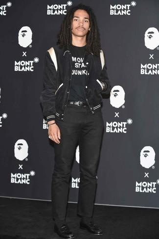 Cómo combinar: mocasín de cuero negro, pantalón chino negro, camiseta con cuello circular estampada en negro y blanco, chaqueta varsity en negro y blanco