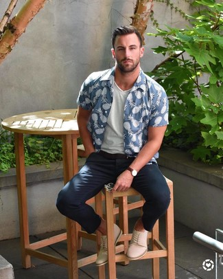 Cómo combinar: botas safari de ante en beige, pantalón chino azul marino, camiseta con cuello en v blanca, camisa de manga corta estampada azul