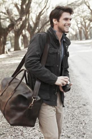 Cómo combinar: bolsa de viaje de cuero en marrón oscuro, pantalón chino en beige, camisa vaquera azul, chaqueta campo negra