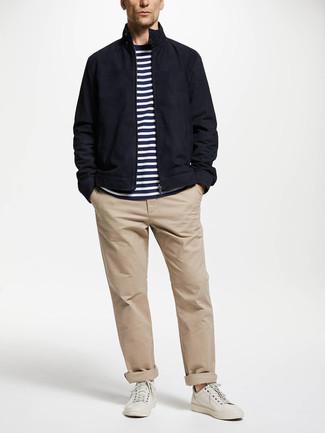 Cómo combinar: tenis de cuero blancos, pantalón chino en beige, camiseta con cuello circular de rayas horizontales en blanco y azul marino, cazadora harrington azul marino