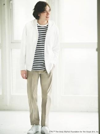 Cómo combinar: tenis de cuero blancos, pantalón chino en beige, camiseta con cuello circular de rayas horizontales en blanco y negro, sudadera con capucha blanca