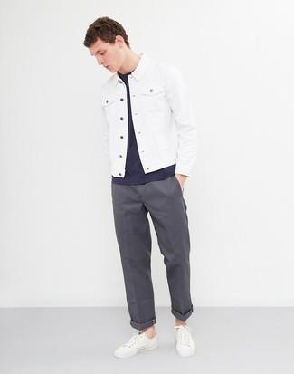 Cómo combinar: tenis de cuero blancos, pantalón chino en gris oscuro, camiseta con cuello circular azul marino, chaqueta vaquera blanca