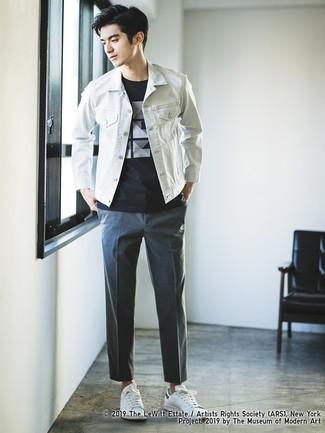 Cómo combinar: tenis de cuero blancos, pantalón chino en gris oscuro, camiseta con cuello circular estampada en negro y blanco, chaqueta vaquera blanca