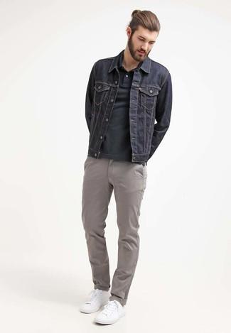 Cómo combinar: tenis blancos, pantalón chino gris, camisa polo negra, chaqueta vaquera azul marino