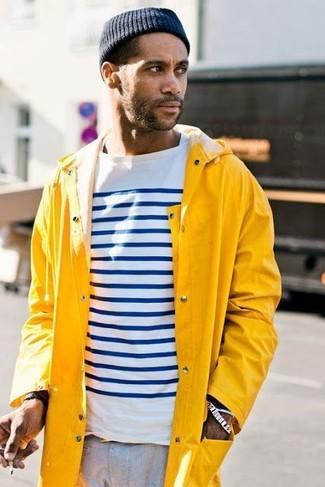 Cómo combinar: gorro azul marino, pantalón chino gris, camiseta de manga larga de rayas horizontales en blanco y azul marino, chubasquero amarillo