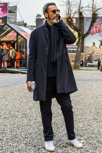 Combinar un abrigo largo negro: Perfecciona el look casual elegante en un abrigo largo negro y un pantalón chino negro. Si no quieres vestir totalmente formal, elige un par de tenis de cuero blancos.
