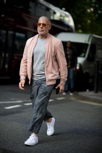 Cómo combinar: tenis de cuero blancos, pantalón chino estampado gris, jersey con cuello circular gris, cazadora de aviador rosada