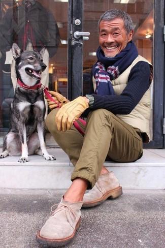 Cómo combinar: botas safari de ante en beige, pantalón chino verde oliva, jersey con cuello circular azul marino, chaleco de abrigo acolchado en beige