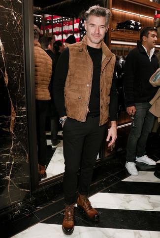 Outfits hombres: Empareja un chaleco de abrigo de ante marrón con un pantalón chino negro para una vestimenta cómoda que queda muy bien junta. Complementa tu atuendo con botas casual de cuero marrónes para mostrar tu inteligencia sartorial.