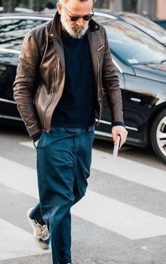 Moda para hombres de 50 años: Utiliza una chaqueta motera de cuero en marrón oscuro y un pantalón chino en verde azulado para un look diario sin parecer demasiado arreglada. ¿Quieres elegir un zapato informal? Opta por un par de deportivas en beige para el día.