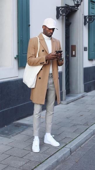 Cómo combinar: tenis de cuero blancos, pantalón chino gris, jersey de cuello alto blanco, abrigo largo marrón claro