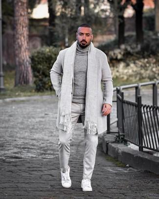 Cómo combinar: tenis de cuero blancos, pantalón chino gris, jersey de cuello alto de lana gris, abrigo largo gris
