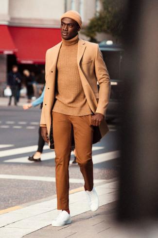 Cómo combinar: tenis de cuero blancos, pantalón chino en tabaco, jersey de cuello alto marrón claro, abrigo largo marrón claro