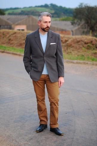 Outfits hombres en primavera 2021: Intenta combinar un blazer en gris oscuro con un pantalón chino en tabaco para lograr un estilo informal elegante. Botas safari de cuero negras son una sencilla forma de complementar tu atuendo. Es una idea genial si tu buscas un atuendo apto para las jornadas de primavera.