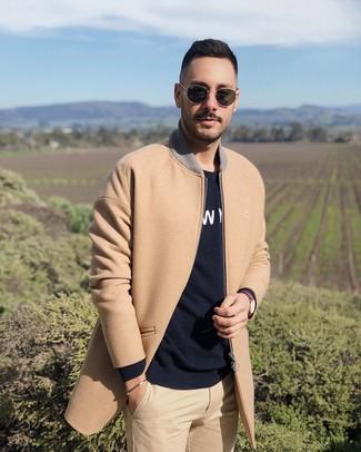 Cómo combinar: gafas de sol negras, pantalón chino marrón claro, jersey con cuello circular estampado en negro y blanco, abrigo largo marrón claro