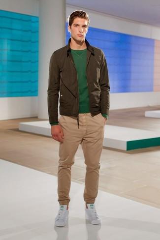 Cómo combinar: tenis de cuero blancos, pantalón chino marrón claro, jersey con cuello circular verde oscuro, cazadora de aviador verde oliva
