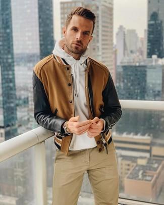 Cómo combinar: reloj de cuero marrón, pantalón chino marrón claro, sudadera con capucha blanca, cazadora de aviador marrón