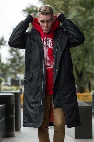 Cómo combinar: pantalón chino marrón claro, sudadera con capucha estampada en rojo y blanco, parka negra
