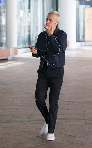Cómo combinar: zapatillas slip-on blancas, pantalón chino negro, camiseta con cuello circular de rayas horizontales en negro y blanco, cazadora de aviador azul marino