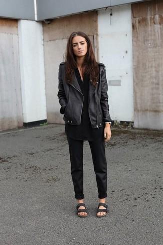 Cómo combinar: sandalias planas de cuero negras, pantalón chino negro, túnica negra, chaqueta motera de cuero negra