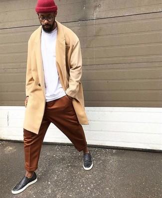 Cómo combinar: zapatillas slip-on de cuero negras, pantalón chino en tabaco, sudadera blanca, abrigo largo amarillo