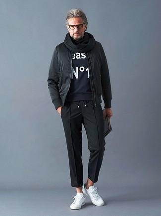 Cómo combinar: tenis de cuero blancos, pantalón chino negro, sudadera estampada azul marino, cazadora de aviador negra