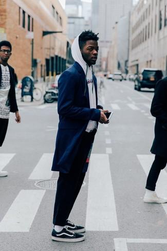 Combinar un pantalón chino azul marino en clima fresco: Usa un abrigo largo azul marino y un pantalón chino azul marino para el after office. Para el calzado ve por el camino informal con tenis de lona verde oscuro.