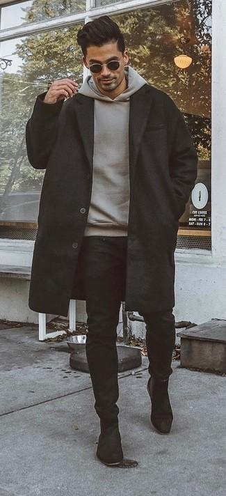 Outfits hombres en otoño 2020: Utiliza un abrigo largo negro y un pantalón chino negro para las 8 horas. Opta por un par de botines chelsea de ante negros para mostrar tu inteligencia sartorial. Para este otoño, es una elección bellísima.