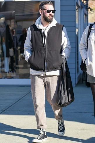Combinar un chaleco de abrigo negro: Considera ponerse un chaleco de abrigo negro y un pantalón chino de pana en beige para cualquier sorpresa que haya en el día. Mezcle diferentes estilos con zapatillas altas de lona en negro y blanco.