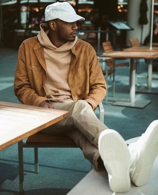 Cómo combinar: tenis de cuero blancos, pantalón chino en beige, sudadera con capucha marrón claro, chaqueta estilo camisa de ante en tabaco