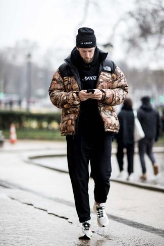Outfits hombres: Intenta combinar un plumífero de camuflaje marrón junto a un pantalón chino negro para un lindo look para el trabajo. Deportivas blancas contrastarán muy bien con el resto del conjunto.