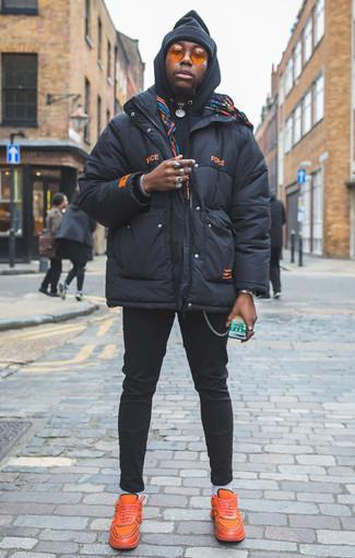 Combinar un plumífero azul marino: Utiliza un plumífero azul marino y un pantalón chino negro para después del trabajo. Si no quieres vestir totalmente formal, opta por un par de deportivas naranjas.