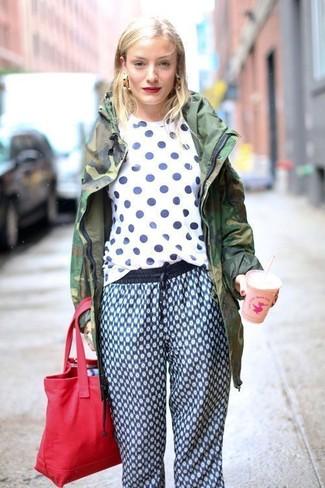 Cómo combinar: bolsa tote de lona roja, pantalón de chándal estampado azul, camiseta con cuello circular a lunares en blanco y azul marino, parka de camuflaje verde oscuro