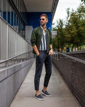 Cómo combinar: zapatillas slip-on de lona azul marino, pantalón de chándal azul marino, camisa de manga larga de rayas verticales en blanco y azul marino, cazadora de aviador verde oscuro