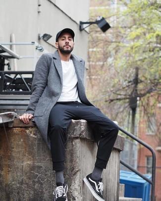 Cómo combinar: tenis de lona en negro y blanco, pantalón de chándal negro, camiseta con cuello circular blanca, abrigo largo gris