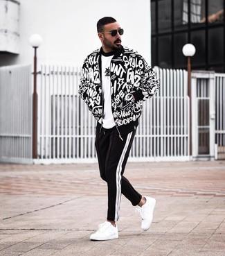 Cómo combinar: tenis de cuero blancos, pantalón de chándal en negro y blanco, camiseta con cuello circular estampada en blanco y negro, cazadora de aviador estampada en negro y blanco