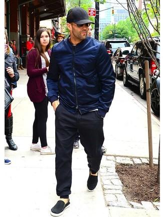 Cómo combinar: zapatillas slip-on de lona negras, pantalón de chándal negro, camiseta con cuello circular blanca, cazadora de aviador azul marino