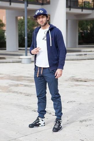 Cómo combinar: zapatillas altas de cuero negras, pantalón de chándal azul marino, camiseta con cuello circular estampada en blanco y negro, sudadera con capucha azul marino