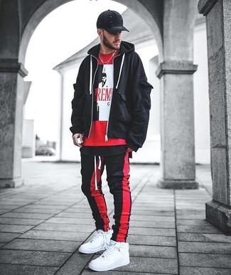 Cómo combinar: zapatillas altas de cuero blancas, pantalón de chándal de rayas verticales en rojo y negro, camiseta con cuello circular estampada roja, sudadera con capucha negra