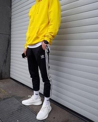 Cómo combinar: deportivas blancas, pantalón de chándal de rayas verticales en negro y blanco, camiseta con cuello circular blanca, sudadera con capucha amarilla