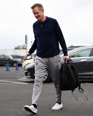 Cómo combinar: zapatillas slip-on de lona a cuadros grises, pantalón de chándal gris, camiseta con cuello circular azul marino, sudadera con capucha azul marino